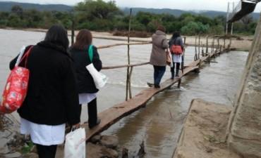 Alumnos y maestras catamarqueñas cruzan una peligrosa pasarela para poder llegar a la escuela