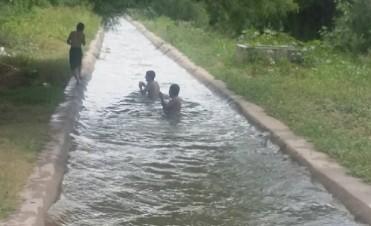 """Niños juegan y se refrescan en el """"canal de la muerte"""""""